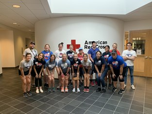 USI students pose in front of the American Red Cross logo while volunteering on Service Saturday
